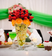 Fruit Marquee Table Centre Piece with contrasting Green Draping in Background