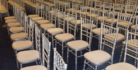 Silver Chiavari Chairs with Ivory coloured Seat Pads in rows