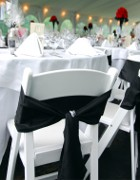 Black Sash on White Foldable Chair inside Marquee